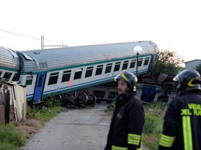 Fire fighters stand next to the twisted wreckage of a train that plowed into a truck last night in Caluso near Turin, Italy