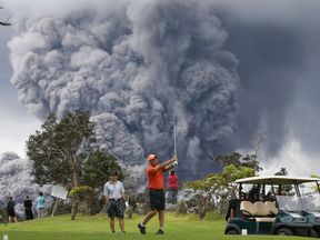 People play golf as an ash plume rises in the distance from the Kilauea volcano on Hawaii's Big Island on May 15, 2018 in Hawaii Volcanoes National Park, Hawaii