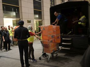 Police take away crates from one of Najib Razak's apartments