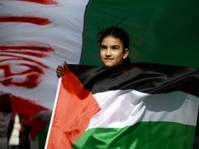 A demonstrator waves a Palestinian flag on Nakba day