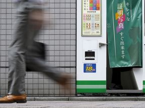 A pedestrian walks past an ID photo machine box as a man sits inside at a business district in Tokyo, September 15, 2015