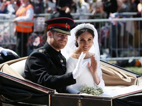 Prince Harry and Meghan Markle ride in an open-topped carriage
