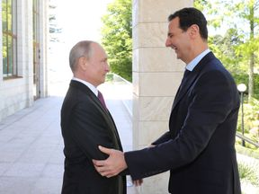 Vladimir Putin welcomes Syrian President Bashar al-Assad during their meeting in the Black Sea resort of Sochi, Russia