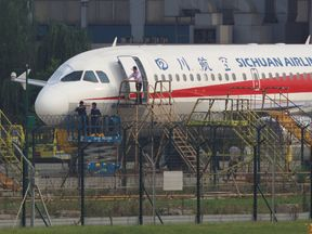 Workers inspect a Sichuan Airlines plane that made an emergency landing after a windshield on the cockpit broke off