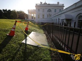 Yellow tape and cones around a sinkhole next to the entrance of the briefing room at the White House