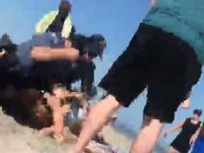 The officer is seen punching the woman who is on the ground