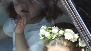 A flower girl waves to the crowd as she rides in a car to the wedding at St George's Chapel in Windsor Castle of Prince Harry and Meghan Markle. PRESS ASSOCIATION Photo. Picture date: Saturday May 19, 2018. See PA story ROYAL Wedding. Photo credit should read: Andrew Milligan/PA Wire