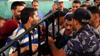 Palestinians crowd to get on a bus going to Egypt after the border was opened in a rare move
