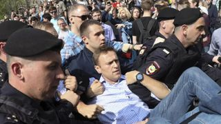 Russian police police carrying struggling opposition leader Alexei Navalny, centre, at a demonstration against President Vladimir Putin in Pushkin Square