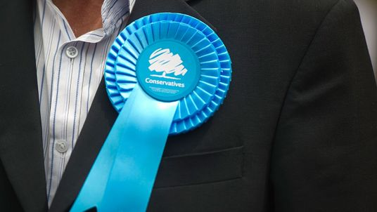 EALING, ENGLAND - MAY 21: A supporter's Conservative rosette on May 21, 2014 in Ealing, England. The rally comes in the final day of campaigning before polls open for the European Parliament election tomorrow. (Photo by Bethany Clarke/Getty Images)