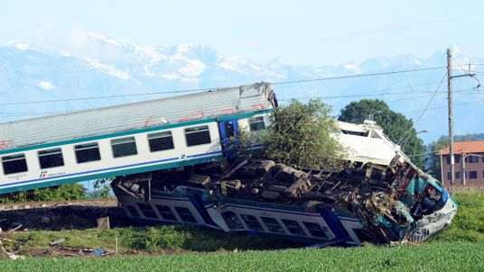 The twisted wreckage of a train that plowed into a truck last night is seen in Caluso, near Turin