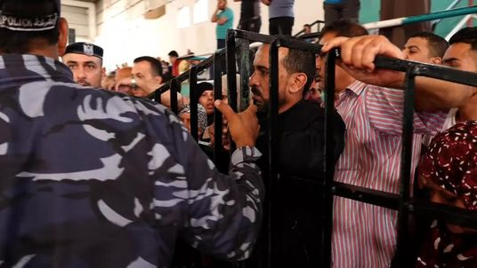 People wait to try to get on a bus leaving Gaza