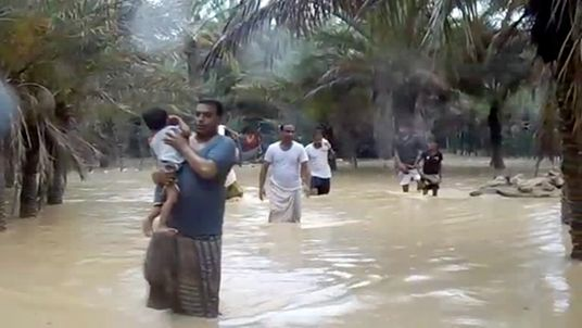 A man clutches a young child as he wades through floodwater in Socotra
