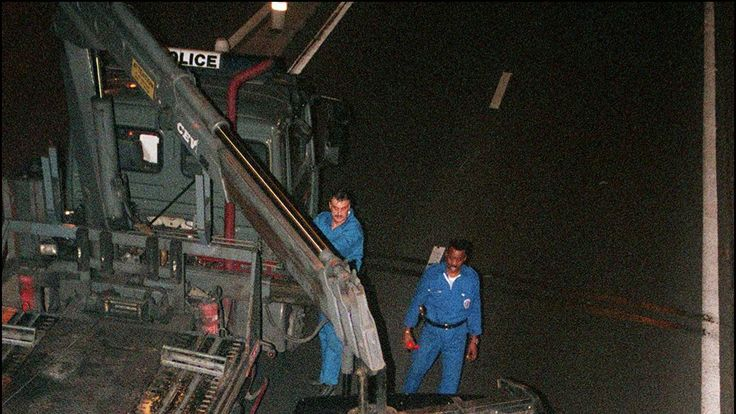 French policemen lift the wreckage of Princess Diana's car in the Alma tunnel of Paris to put it in a truck.