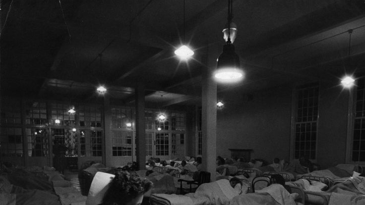 A night nurse sits in the ward of a mental hospital in 1956
