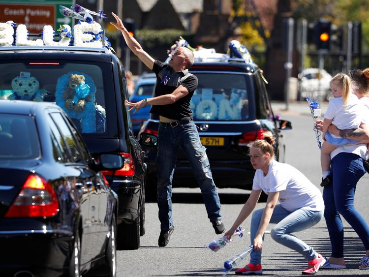 Well-wishers throw flowers during the funeral procession