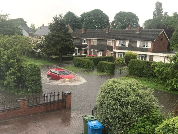 A car drives through a flooded street in Staffordshire after heavy rain over the Bank Holiday weekend. Credit: Twitter/Jaynie_g