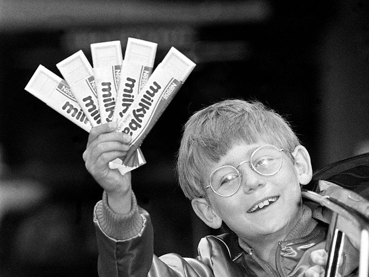 """Nestle's new and 7th Milky Bar kid, Antony Eden, nine, with a fistful of the white chocolate bars, setting out to see London by limousine, after beating 2,500 young hopefuls wanting to say the final line """"The Milkybars are on me!"""" in TV commercials."""