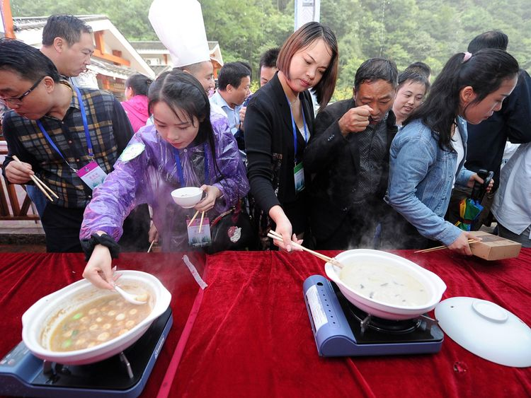 People eating dishes made from Salamander at a Chinese food festival in Hunan province