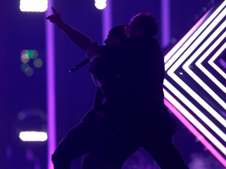 """Security subdues a person who invaded the stage as United Kingdom's SuRie performed """"Storm"""" during the Grand Final of Eurovision Song Contest 2018 at the Altice Arena hall in Lisbon, Portugal, May 12, 2018. REUTERS/Pedro Nunes"""