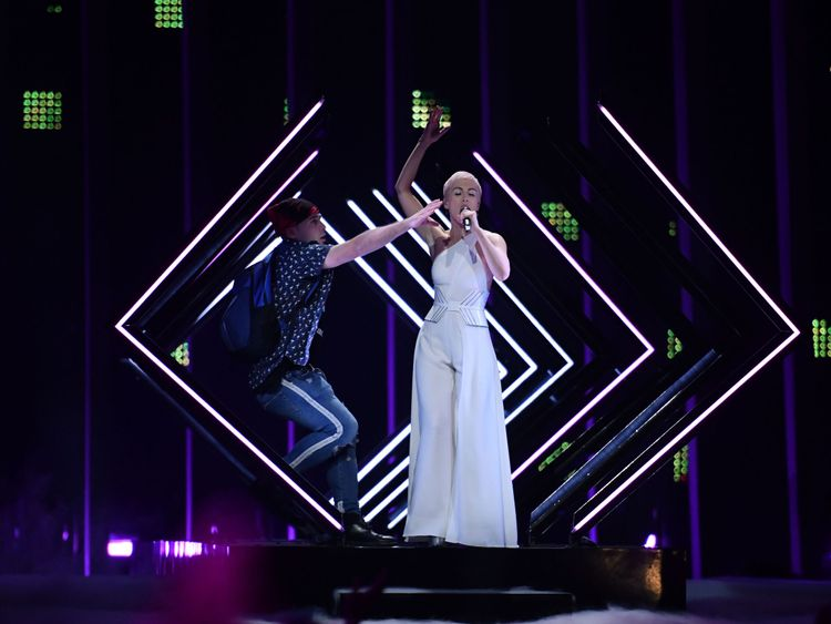 A man takes the microphone from Britain's singer Susanna Marie Cork aka SuRie as she performs 'Storm' during the final of the 63rd edition of the Eurovision Song Contest 2018 at the Altice Arena in Lisbon, on May 12, 2018. (Photo by Francisco LEONG / AFP) (Photo credit should read FRANCISCO LEONG/AFP/Getty Images)