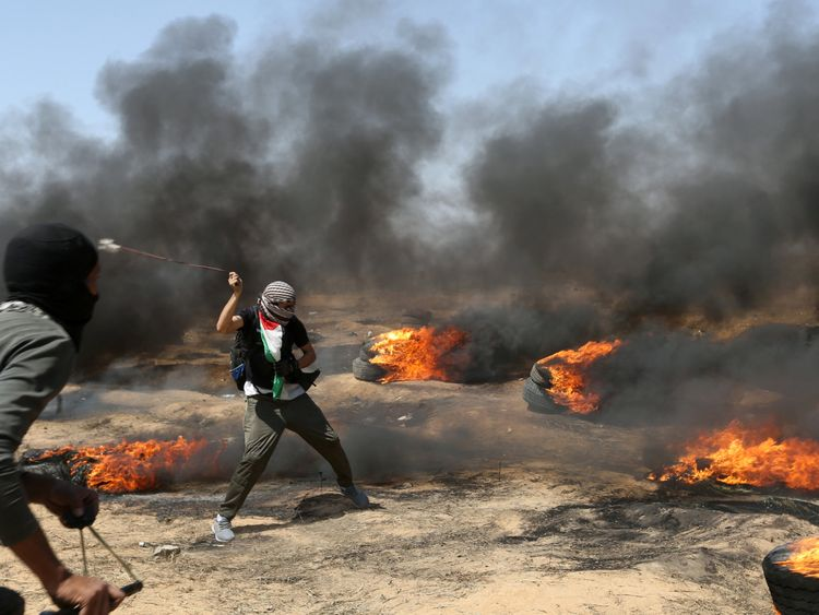 A demonstrator uses a sling to hurl stones at Israeli forces