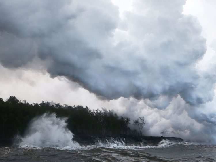 A toxic steam plume filled with shards of volcanic glass rises from the Pacific Ocean as lava hits the water
