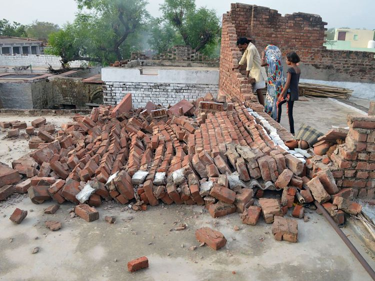 Indian residents look at a wall damaged by high winds during a major dust storm in Agra district in northern India's Uttar Pradesh state