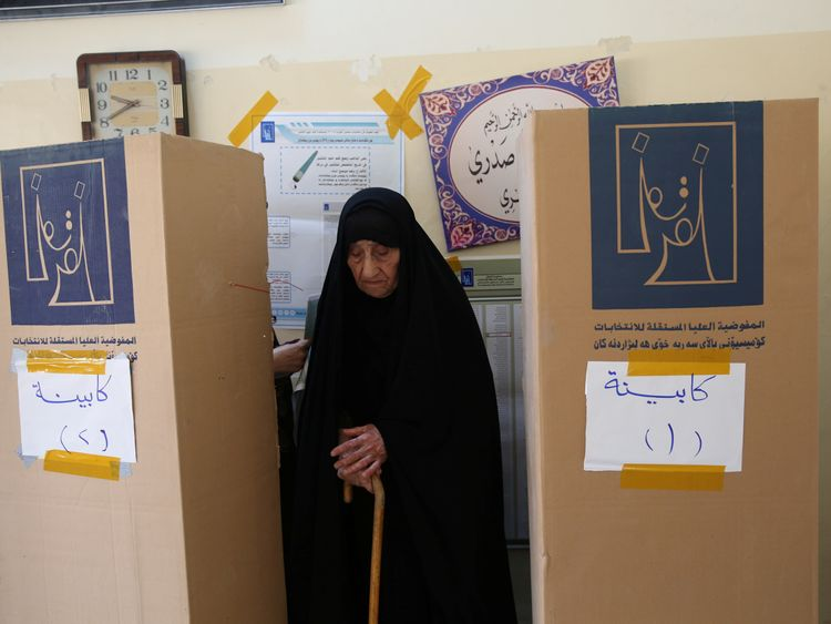 An Iraqi woman prepares herself to cast her vote at a polling station during the parliamentary election in Baghdad