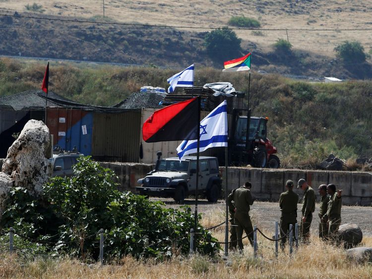 Israeli soldiers walk among armoured vehicles in the Israeli-occupied Golan Heights,