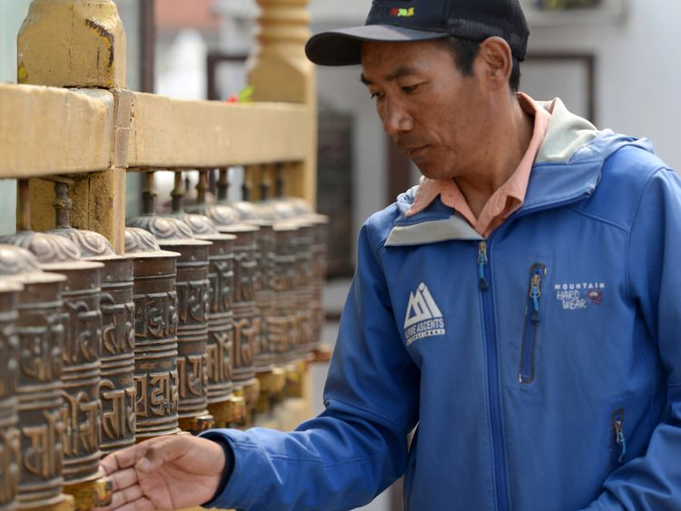 Nepali mountaineer Kami Rita Sherpa spinds prayer wheels at Boudhanath Stupa where he has a rented room on the outskirts of Kathmandu.- Two Nepali Sherpas broke their own world records for the most Everest