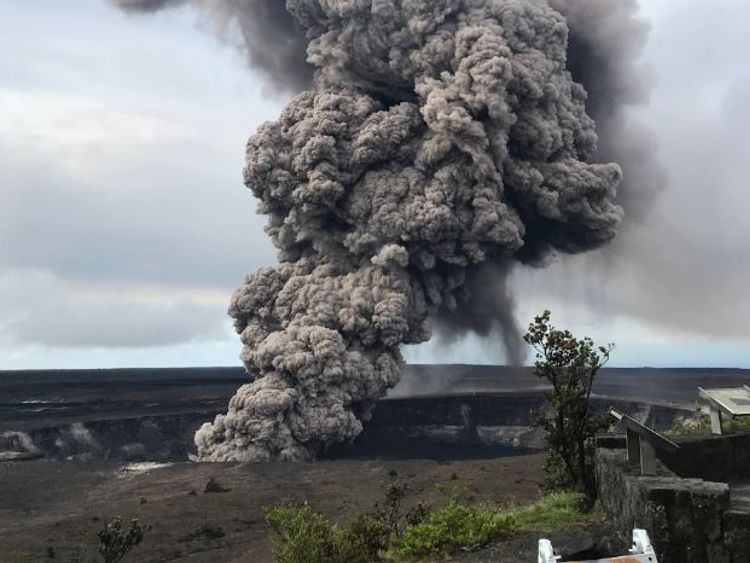 An ash column rises from the volcano