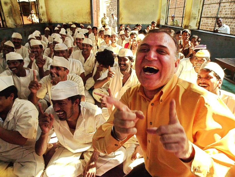 Dr Madan Kataria, pictured here leading prisoners in laughter yoga, created the therapy