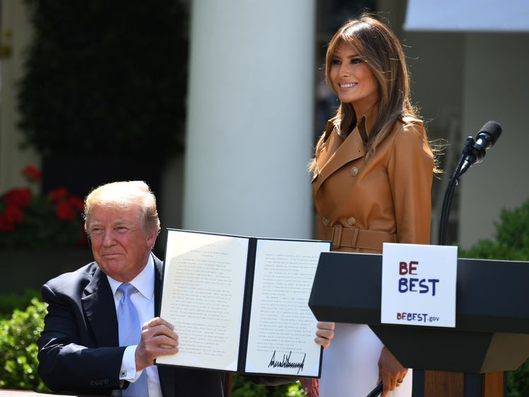 First Lady Melania Trump smiles as US President Donald Trump holds up his proclamation for 'National Be Best Day'