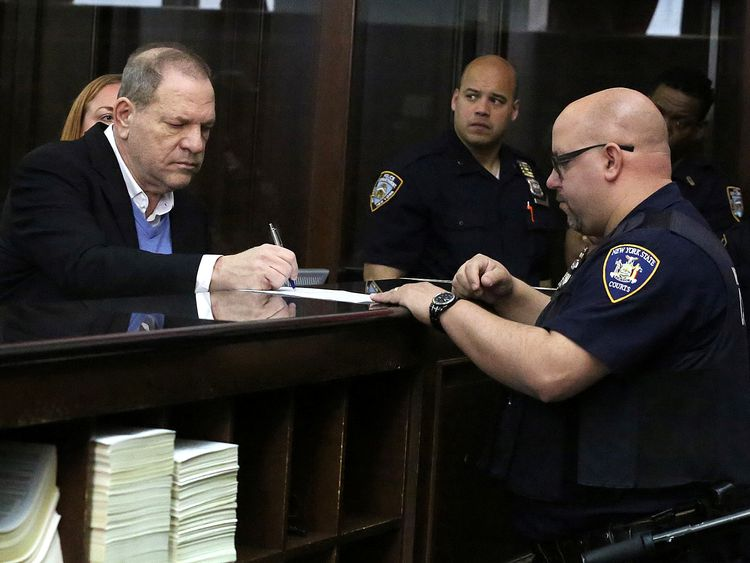 Film producer Harvey Weinstein signs papers inside Manhattan Criminal Court during his arraignment in Manhattan in New York