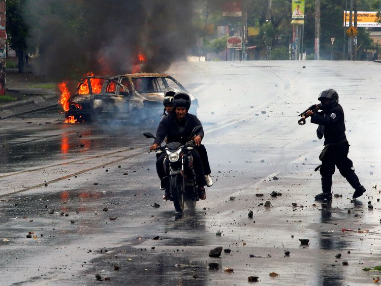 A riot police officer fires his shotgun towards two men during a protest against Nicaragua's President Daniel Ortega's government in Managua