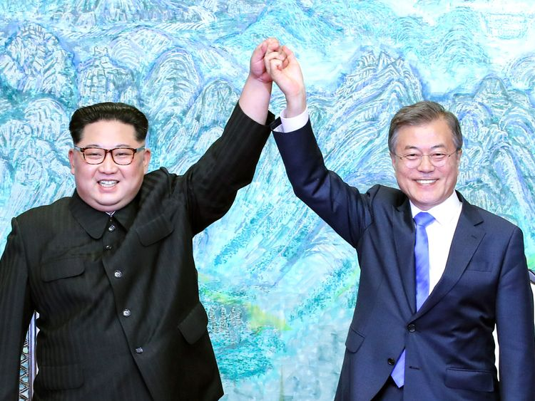 Kim Jong Un (L) and Moon Jae-in (R) raise their hands during a signing ceremony