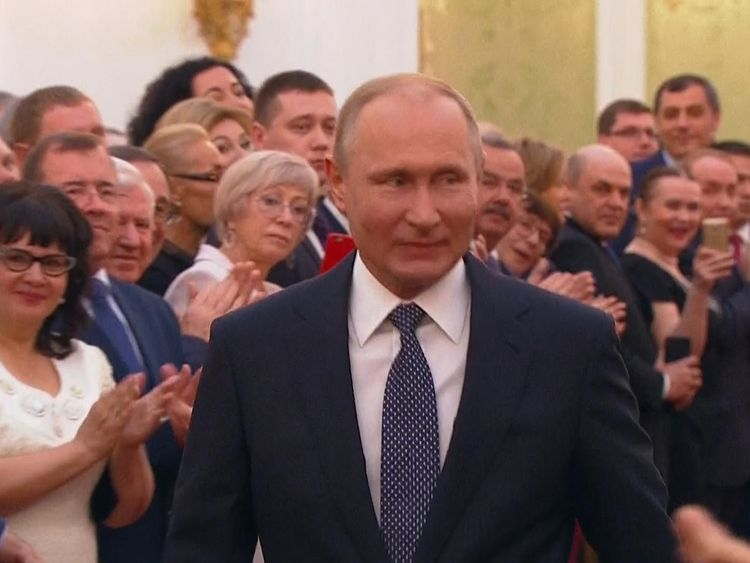 Putin smiles at attendees in the Great Kremlin Palace
