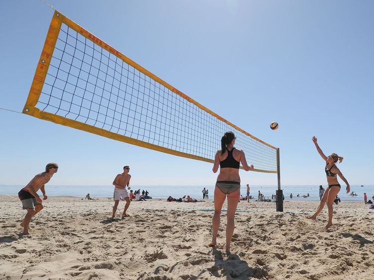 People take part in a game of beach volleyball on Boscombe beach in Dorset