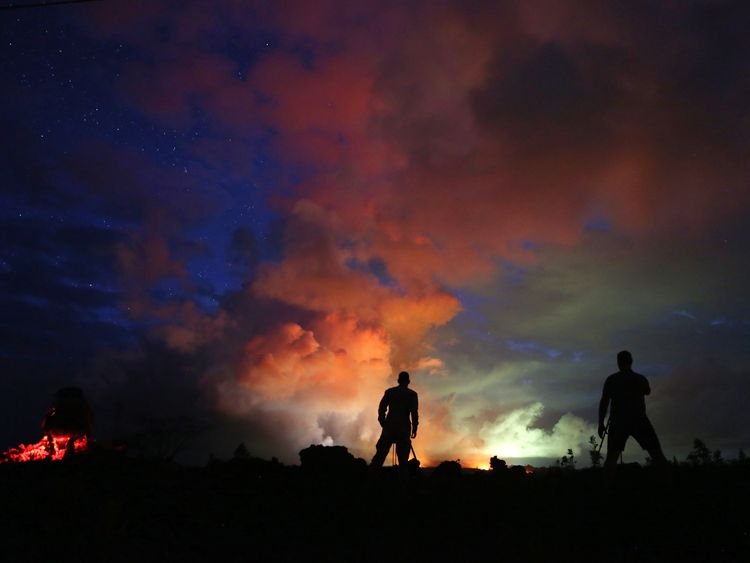 Photographers look on as lava from active fissures illuminates volcanic gases