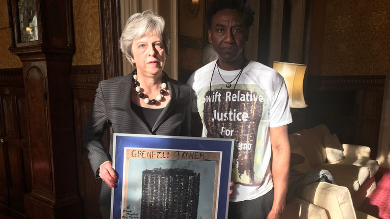 Mrs May posed with the artist Damel Carayol who presented her with a print of his artwork Credit: Damel Carayol