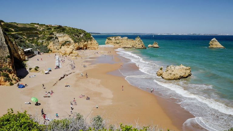 People enjoy the warm weather at the Dona Ana beach in Lagos on April 18, 2018 in the southern Portugal region of Algarve