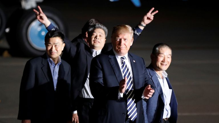 The three Americans formerly held hostage in North Korea gesture next to U.S.President Donald Trump, upon their arrival at Joint Base Andrews