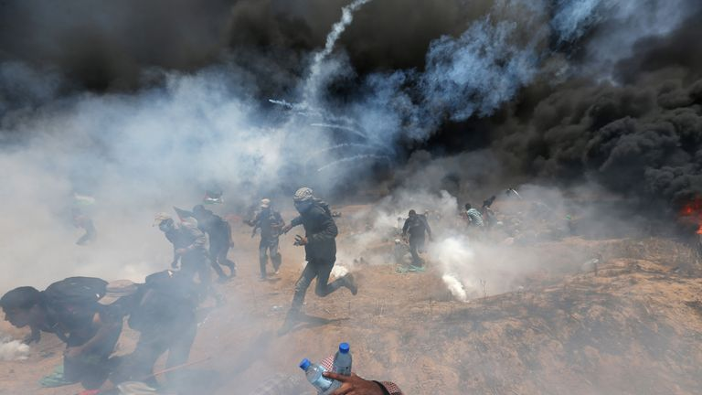 Palestinian demonstrators run for cover from Israeli fire and tear gas during a protest against U.S. embassy move to Jerusalem and ahead of the 70th anniversary of Nakba, at the Israel-Gaza border in the southern Gaza Strip May