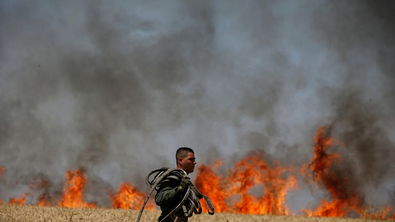 An Israeli soldier carries a hose as he walks in a burning field on the Israeli side of the border fence between Israel and Gaza near kibbutz Mefalsim, Israel, May 14, 2018