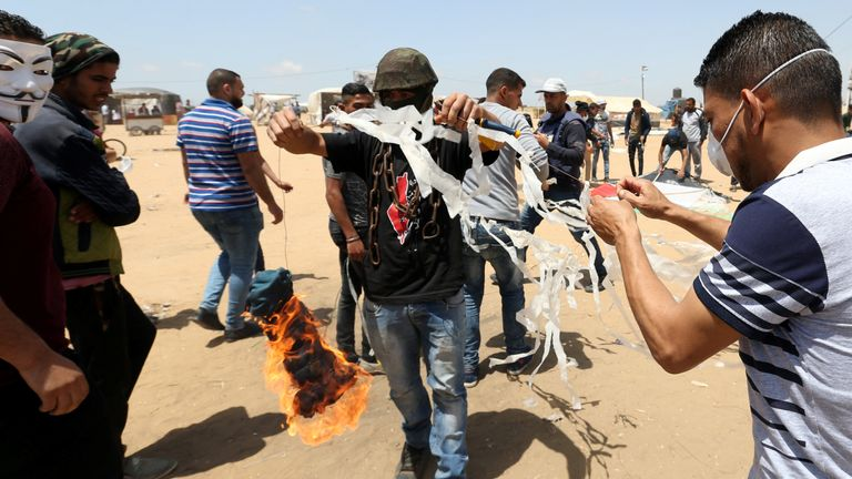 Palestinian demonstrators prepare to set a kite on fire to be thrown at the Israeli side