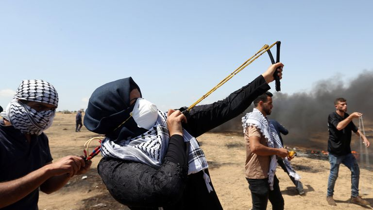 A female demonstrator uses a slingshot to hurl stones at Israeli forces