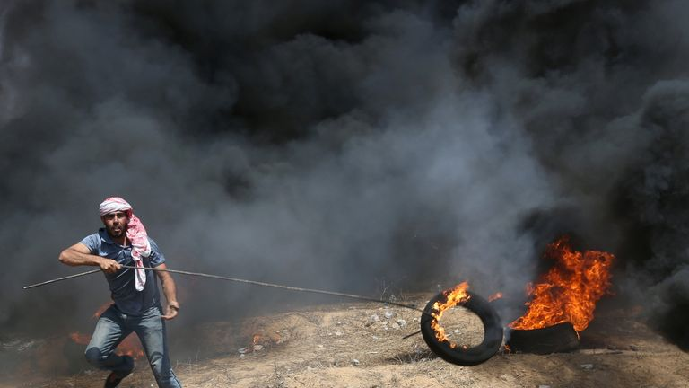 A demonstrator moves a burning tire