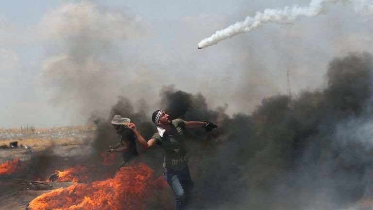 A demonstrator uses a tennis racket to return a tear gas canister fired by Israeli troops