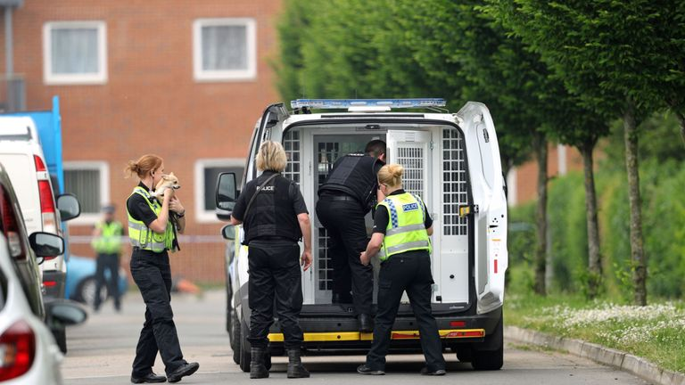Police officers remove a dog from the scene in Dexter Way, Gloucester